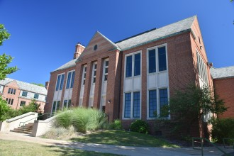 This is a photo of the exterior of Walwood Hall. The building is two stores tall on the west side, and three stories tall on the east side. The sides of the building are red brick and they are topped with a grey roof. Wallwood hall was built in 1939 for the dual role as a student union and the first dormitory on campus.