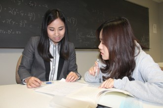 Two asian female students work together, one tutoring the other with the aid of reference books and notes, the board behind them filled with formulas. You too can engage in learning with others at Western Michigan University.