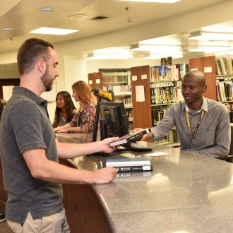 Student helping a patron at library service desk.