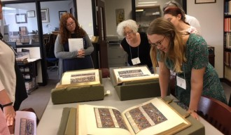 Class attendees looking at medieval manuscripts in Rare Book Room.