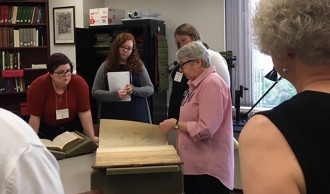 Class attendees looking at a large medieval manuscript.