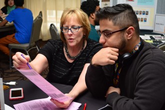 An advisor assists an international student during walk-in advising hours