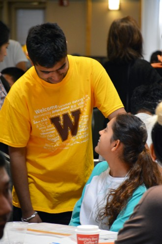 Student volunteer helps to answer a question of a new international student