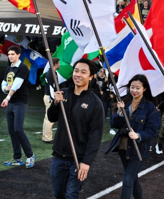 International student holds flag from his home-country during the Annual Homecoming Parade of Flags