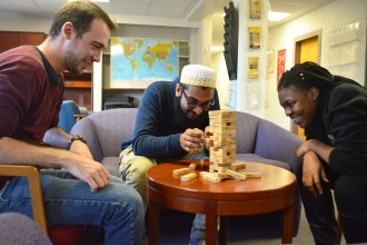 Domestic and international students enjoy a game of Jenga in the common room of their housing.