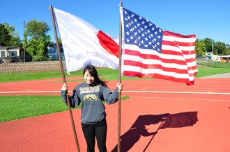 Japanese exchange student in a WMU sweatshirt smiles while holding Japanese and U.S. American flag.