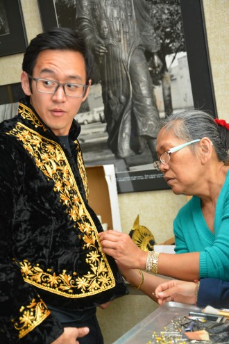 A Malaysian students receives help with his clothing from an older Malaysian community member.