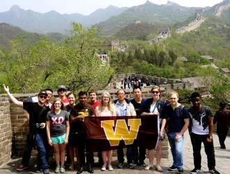 Group of WMU students with the WMU flag standing on the Great Wall of China.