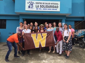 Group of WMU students with the WMU flag in front of the Centro de Salud Integral in the Dominican Republic.