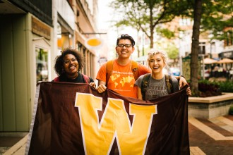 Decorative: Three students holding a W flag in downtown Kalamazoo.