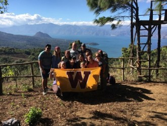 Group of WMU students with the WMU flag in front of Lake Atitlan, Guatemala