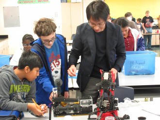 Dr. Matsumura works on a robot with two male high school students.