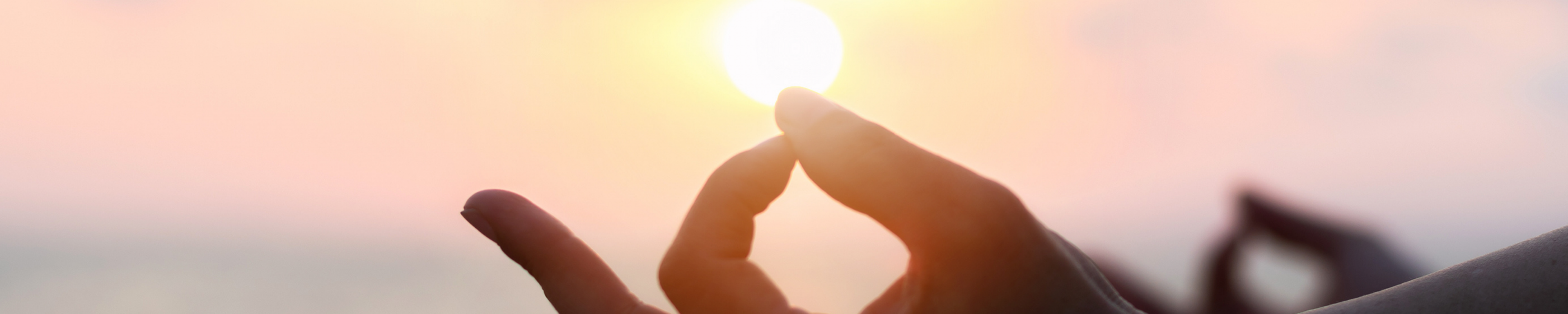 hand in a yoga mudra position resting on a knee in a silhouette against a sunset