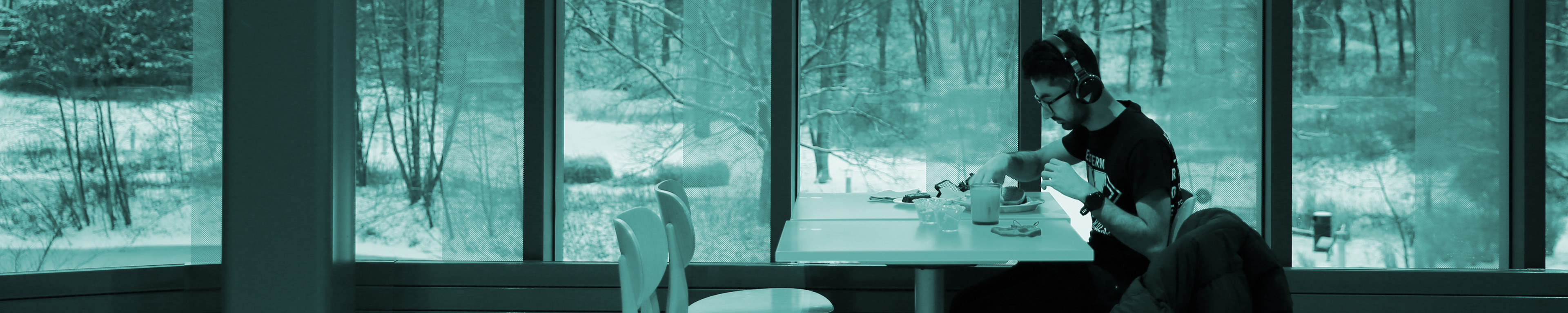 Student sitting by window in Valley Dining Center, snowy background