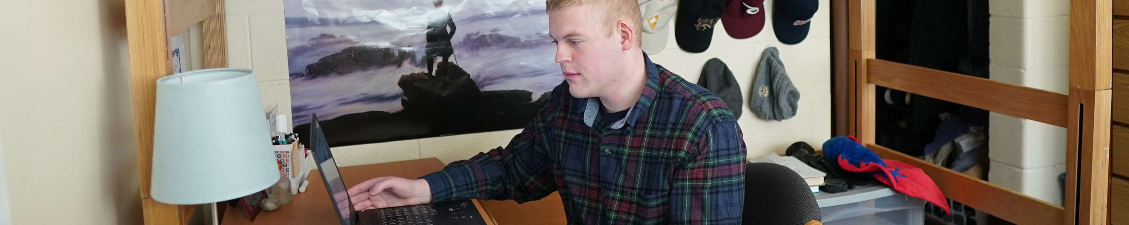 student with laptop at desk in their residence hall room