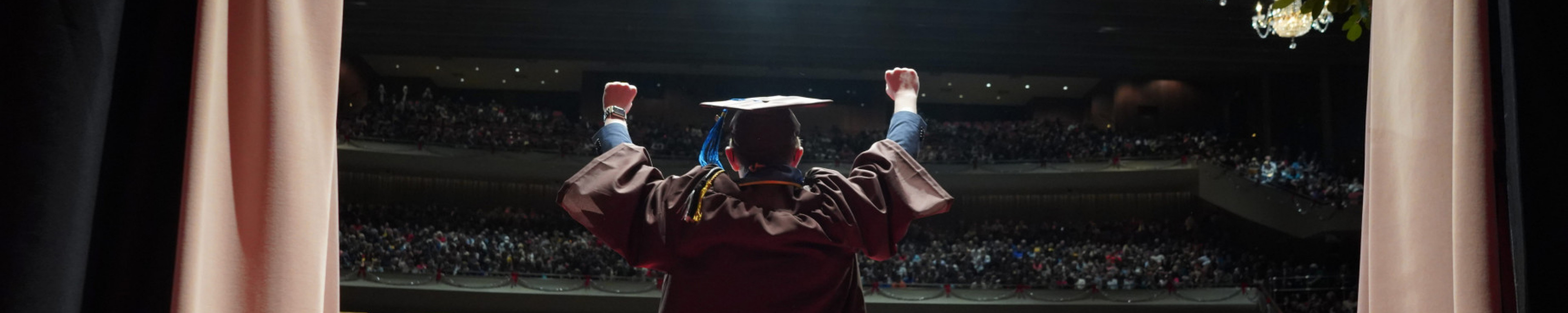 A graduate holds his arms up as he walks onto the stage.