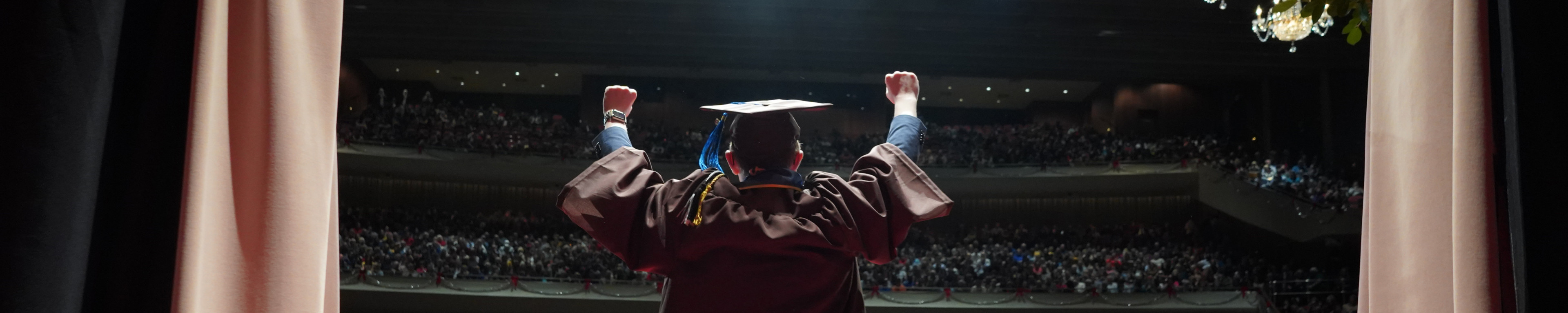 A graduate celebrates with arms outstretched.