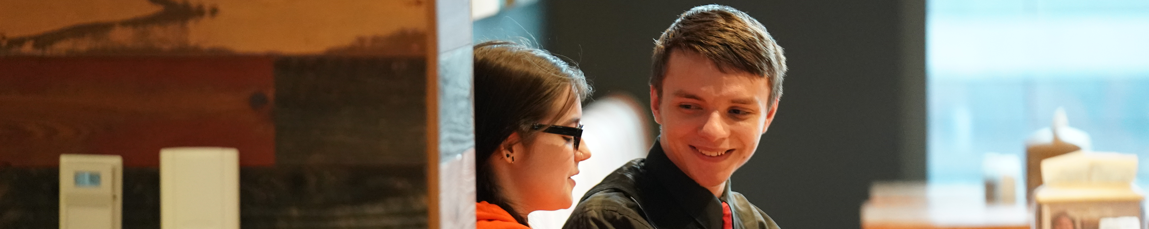 Banner image: two students having a fun conversation while sitting at a table