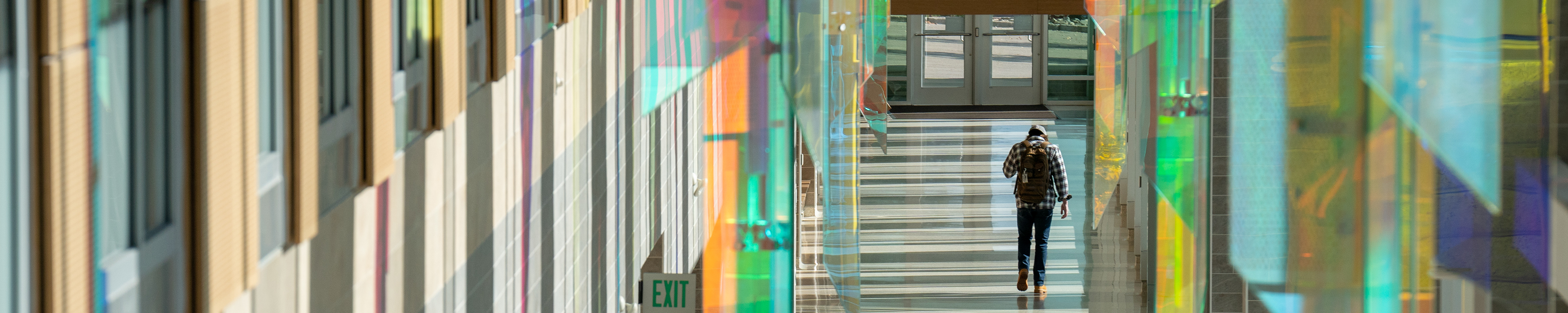 Page banner: student walking in the main area of Sangren Hall on campus