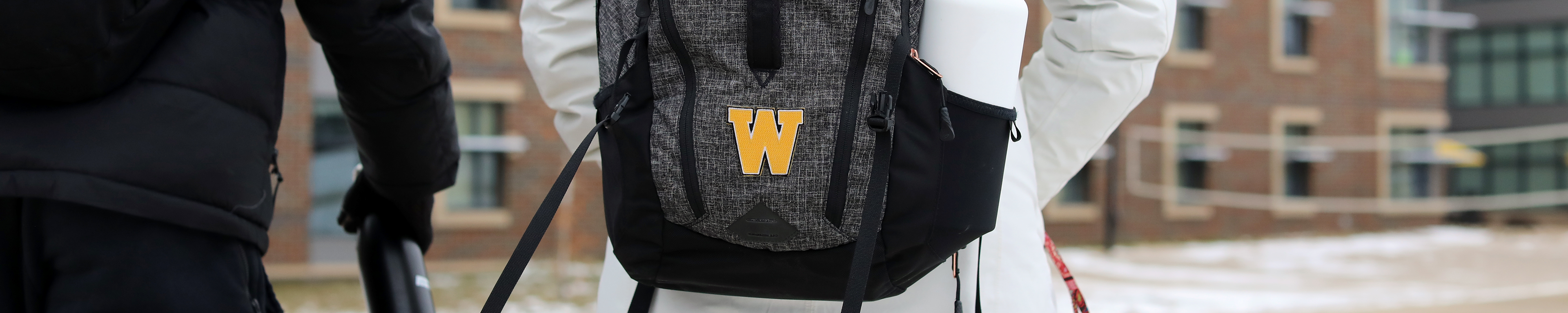 Page banner: students walking with WMU logo on backpack