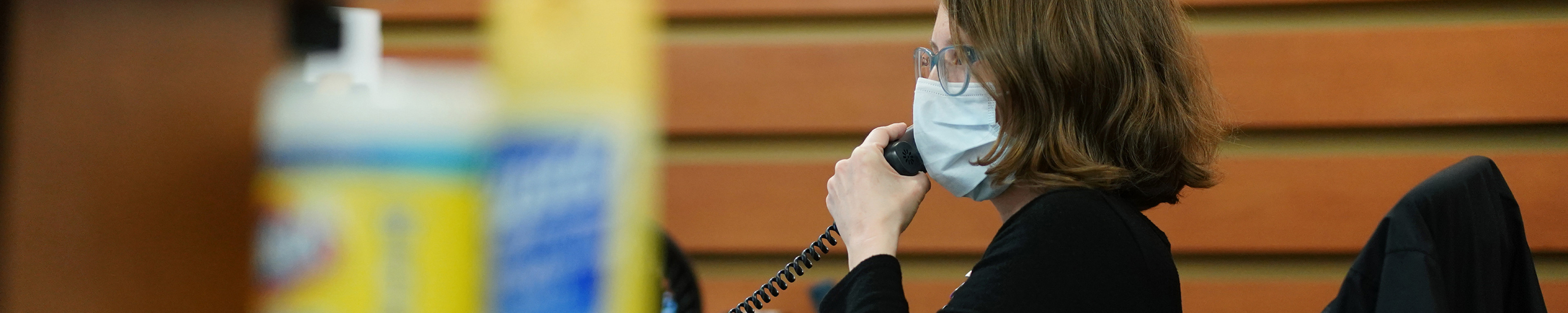 A woman wearing a mask on the phone near some cleaning supplies.