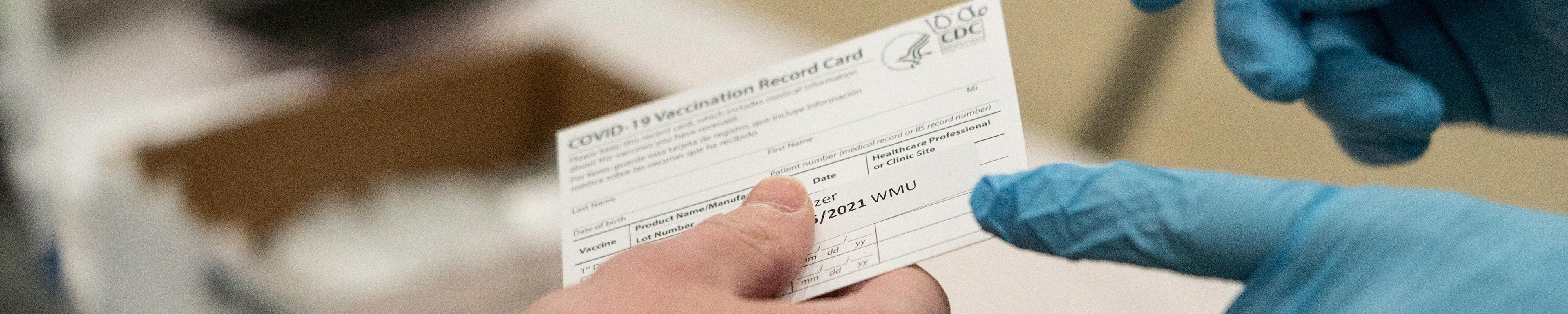 A nursing handing a vaccination record card to someone.