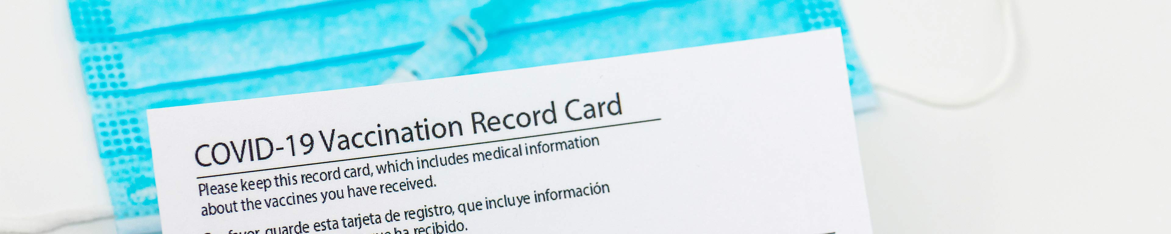 A vaccination record card resting on top of a mask near a syringe.
