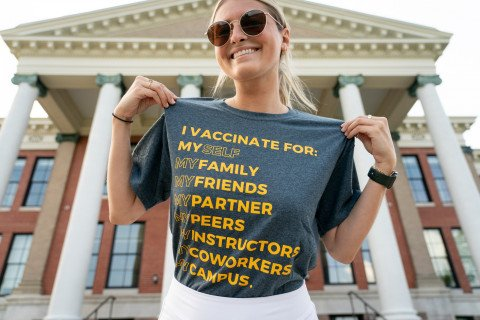 A woman wearing a shirt that reads: I vaccinate for: Myself, my family, my friends, my partner, my peers, my instructors, my coworkers, my campus.