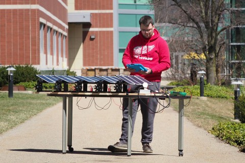 Photo of WMU student Steven Spannagel operating a scaled-down solar panel.
