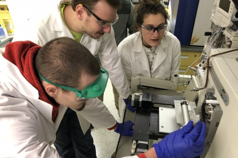 Students analyze a sample in a lab using a mass spectrometer.