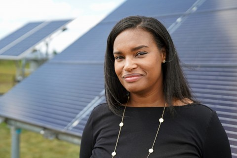 A profile photo of Brandy Brown standing in front of a solar array.