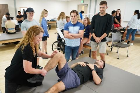 Fruth manipulating a student's leg.