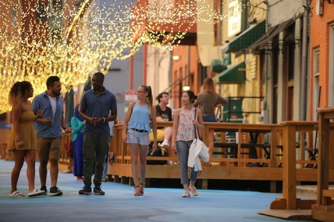 A group of students walks underneath strings of lights in Bates Alley.