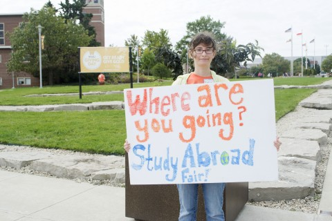 Photo of a student holding a sign which reads, Where are you going? Study Abroad Fair!