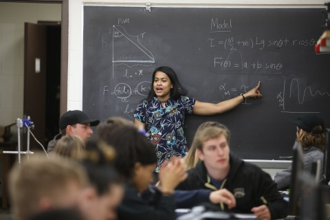 An instructor points to physics equations on a chalkboard.