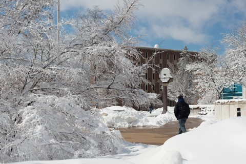 Bundled-up student walking on a cleared sidewalk after a heavy snow.