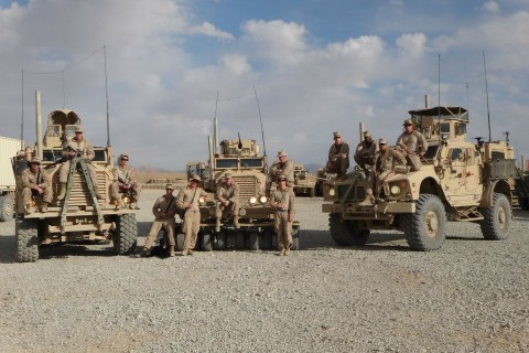 Troops in the Marine Corps stand in front of military vehicles in Afghanistan.