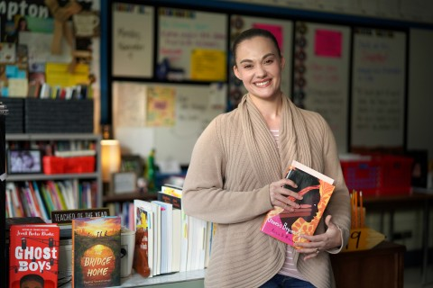 Teacher Stephanie Hampton stands in front of the desk in her classroom holding a book.