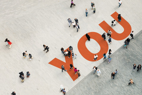 The word YOU written in large orange letters on the street, with people walking around