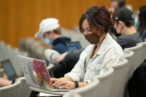 Masked student sitting at laptop