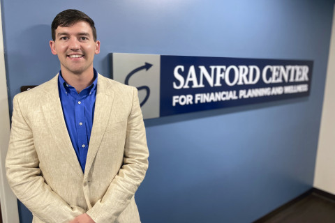 Eldon McCabe standing in front of Sanford Center for Financial Planning and Wellness sign