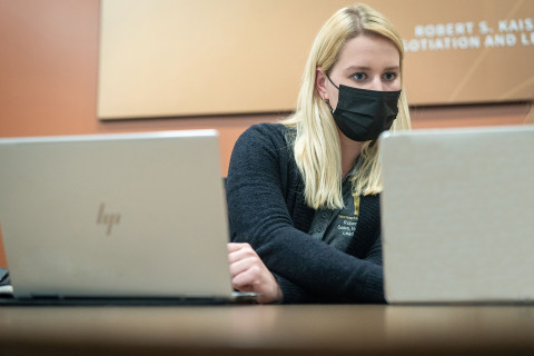 Student wearing mask sitting in front of laptop