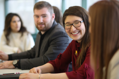 MBA students sitting at table smiling