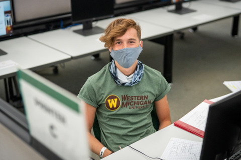 Masked student sitting in front of computer