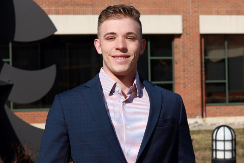 Tyler Earnst, dressed in a suit jacket, smiles and stands in the Haworth College of Business courtyard.