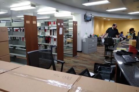 Unpacking items behind service desk at Waldo Library.