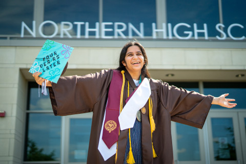 Keshavi Davé stands in her graduation attire with her arms outstretched.