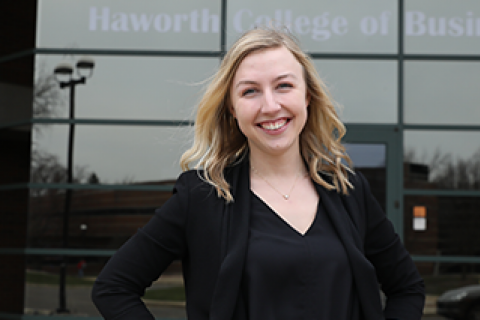 WMU Student smiling in front of the Haworth College of Business