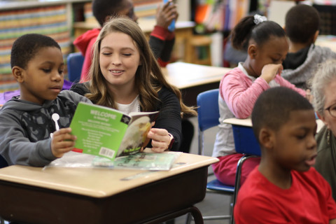 A WMU student helps an elementary school student to read a book