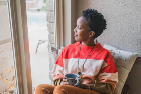 Tabitha Mpamira sitting on couch by window holding cup of coffee